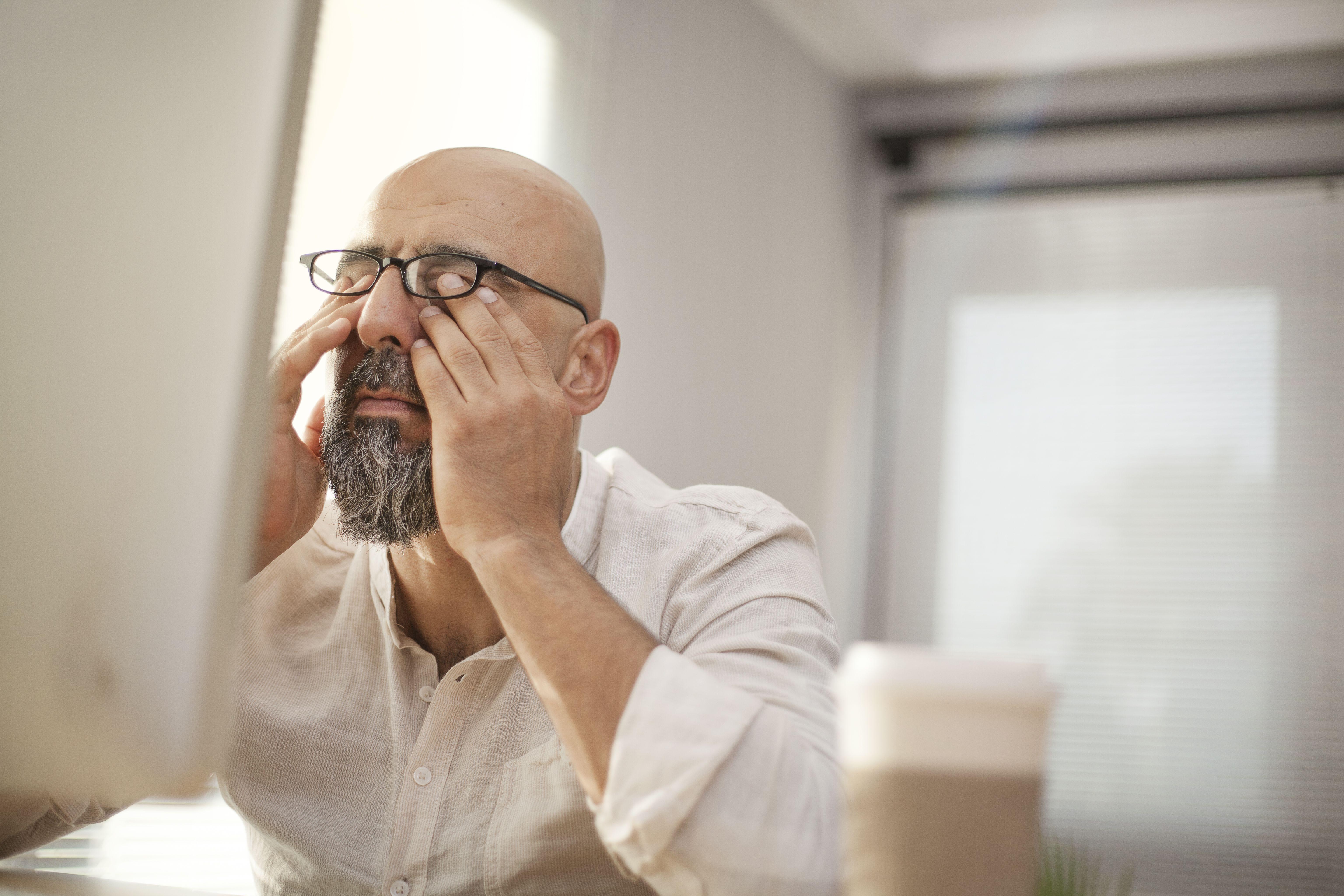 Mann reibt seine müden Augen vor dem PC