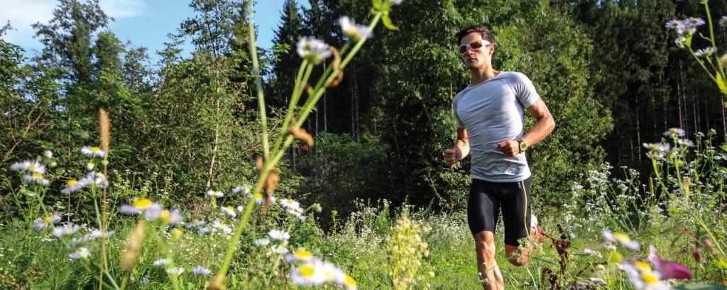 Sportler läuft durch eine Wiese