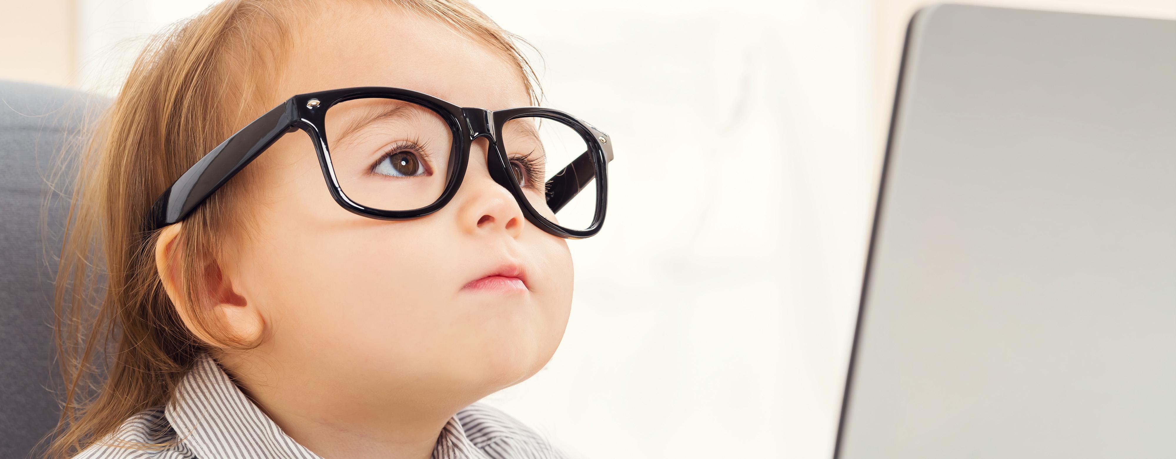 Kind mit Brille vor einem Laptop